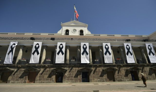 Banners with black ribbons in memory of the kidnap victims hang outside the presidential palace in Quito