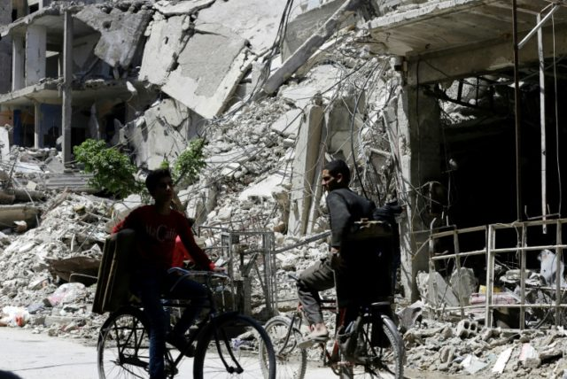 Syrians cycle along a damaged street in Douma on the outskirts of Damascus on April 16, 2018 during an organised media tour after the Syrian army declared that all anti-regime forces have left Eastern Ghouta