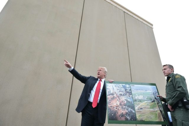 US President Donald Trump examines a prototype of the wall he wants to build along the frontier with Mexico, during a visit to San Diego in March