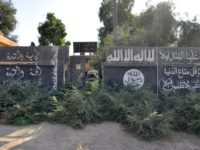 A picture taken on October 20, 2017, shows Islamic State group slogans on a wall in the Syrian town of Mayadeen