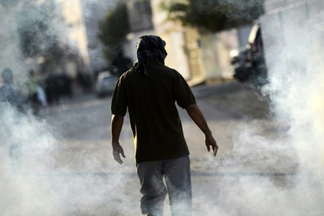 A Bahraini demonstrator walks through teargas fired by security forces during clashes following a demonstration against the government in the village of Sitra, south of Manama, on January 1, 2016