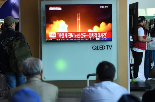 People at a railway station in Seoul watch television news showing file footage of a North Korean missile launch