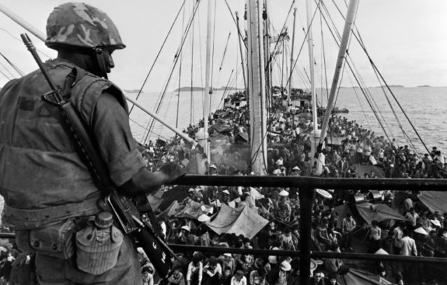 A US soldier watching South Vietnamese refugees crowding a US Navy boat off the coast of Vietnam at the end of Vietnam War