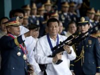 President Rodrigo Duterte (C with outgoing police chief Ronald dela Rosa L) has overseen a bloody anti-drug war that has killed more than 4,000 people
