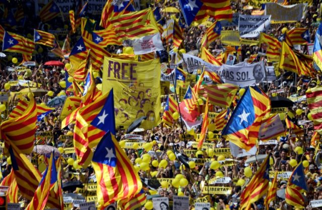 """People wave Catalan pro-independence """"estelada"""" flags during a demonstration to support Catalan pro-independence jailed leaders and politicians in Barcelona on April 15, 2018"""