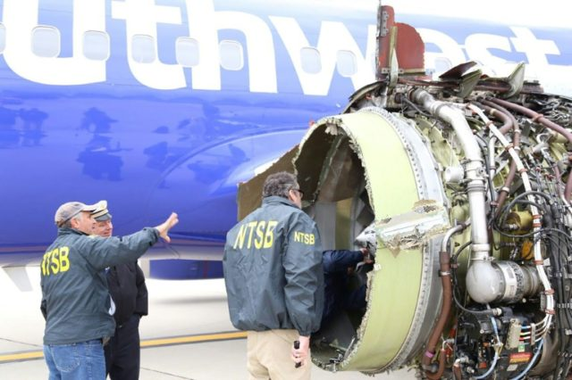 National Transportation Safety Board investigators examine damage to a Southwest Airlines plane that suffered catastrophic engine failure on April 17, 2018, killing a mother of two and forcing an emergency landing