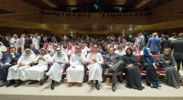 A picture provided by the Saudi Royal Palace on April 18, 2018, shows Saudi Information Minister Awwad Alawwad (C) holding a bucket of popcorn as he attends a test screening at the AMC cinema in Riyadh ahead of the first public film screening in 35 years
