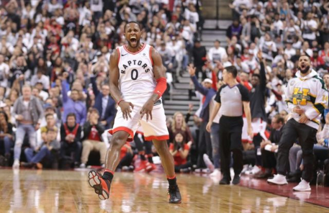 C.J. Miles #0 of the Toronto Raptors celebrates after making a three-pointer as rap artist Drake celebrates on the sideline against the Washington Wizards during Game One of the first round of the 2018 NBA Playoffs in Toronto