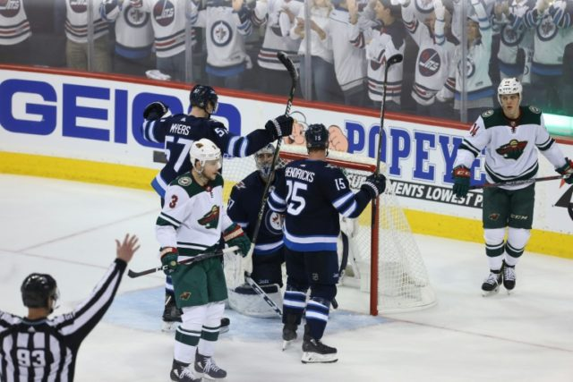 Tyler Myers(L), Connor Hellebuyck (C) and Matt Hendricks of the Winnipeg Jets celebrate a 5-0 victory over the Minnesota Wild to clinch their first playoff series win in franchise history