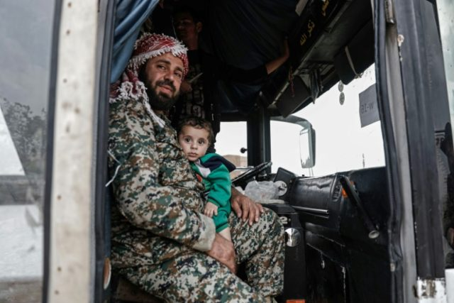 A Syrian rebel fighter evacuated from the town of Dumayr, east of the capital Damascus, holds his son while sitting in a bus upon arriving in the city of Azaz in the northern countryside of Aleppo on April 20, 2018