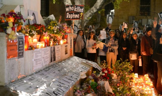 People hold portraits as they stand beside lighted candles placed in memory of murdered journalist Daphne Caruana Galizia on the sixth month anniversary of her death at a makeshift memorial outside the law courts in Valletta, Malta on April 16, 2018