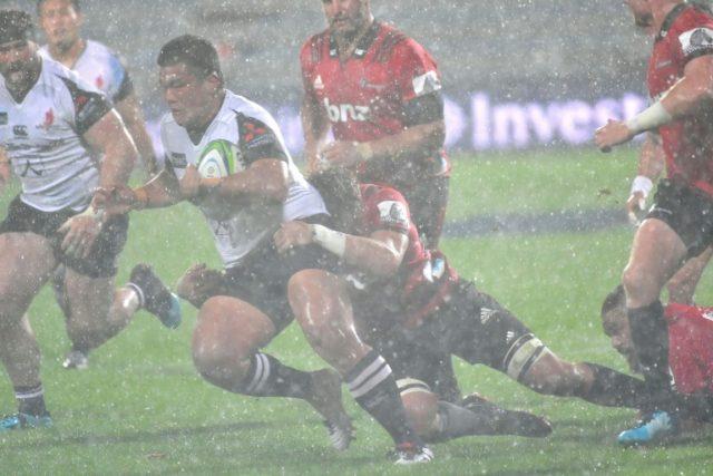 Sunwolves' Koo Ji-woo is tackled by Crusaders' Ethan Blackadder as a massive hailstorm rages in Christchurch