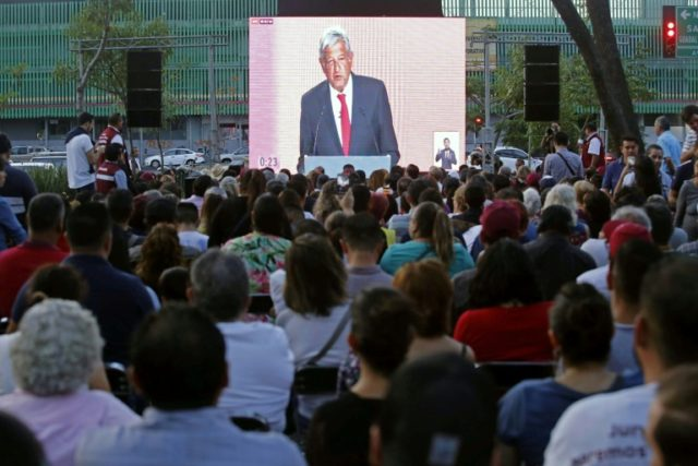 People watch a public television screen showing Mexico's presidential candidate for the MORENA party, Andres Manuel Lopez Obrador (C) during the first presidental debate