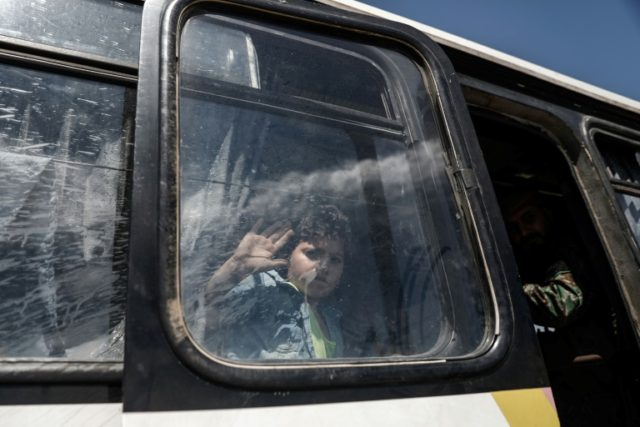 A Syrian boy waves from inside a bus transporting fighters and their families from al-Ruhaiba and eastern Qalamun, upon arriving at a checkpoint in the city of al-Bab in the northern countryside of Aleppo on April 22, 2018