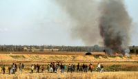 Palestinians demonstrate along Gaza's border with Israel as smoke rises from a field set on fire by a molotov cocktail delivered by kite from the coastal territory