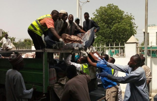 People unload from a truck to a morgue the bodies of victims in Bama, Borno State, northeastern Nigeria, on April 22, 2018, following twin suicide blasts inside of a mosque