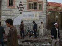 Residents inspect the site of a suicide bombing outside the voter registration centre