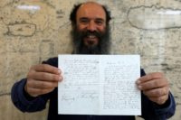 Meron Eren, co-founder and owner of the Kedem auction house, holds a letter by German anti-Semitic composer Richard Wagner which will be auctioned in Jerusalem next week