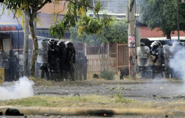 Riot police agents clash with students during protests against government's reforms in the Institute of Social Security (INSS) in Managua on April 21, 2018