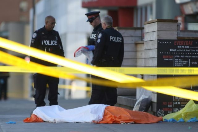 Police officers stand near one of the bodies on the street after a truck drove up on the curb and hit several pedestrians in Toronto