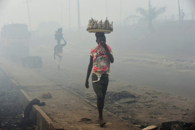 Vendors cover their nose as they walk through smoke emanating from the Olusosun dump site in Lagos, Nigeria's commercial capital