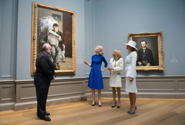 Mary Morton (2nd-L), head of the department of French paintings, speaks with US First Lady Melania Trump (R) and French First Lady Brigitte Macron, alongside senior curator Franklin Kelly at the National Gallery of Art's Paul Cezanne portraits show
