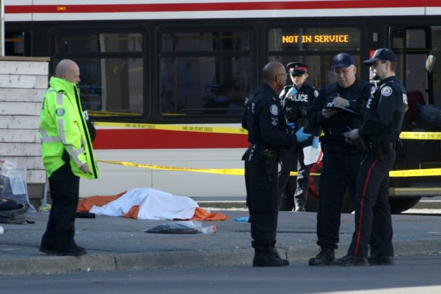 Police stand near one of the bodies on the street after a man drove a van into a crowd of pedestrians in Toronto killing at least 10 and injuring 15