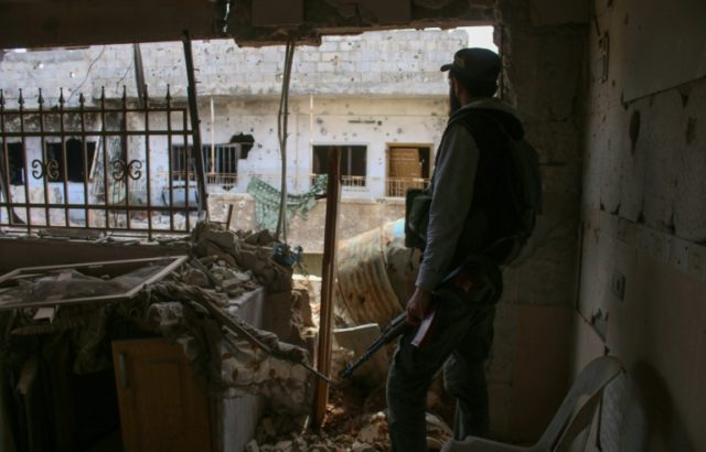 An opposition fighter looks out from a destroyed building in a rebel-held area in the southern Syrian city of Daraa