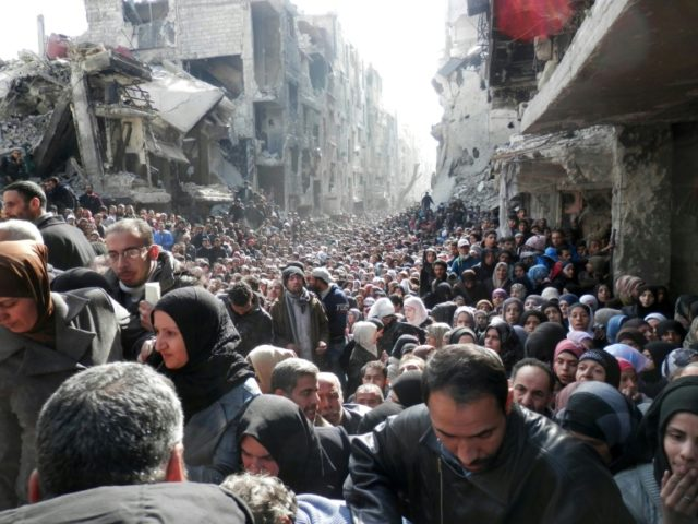 Residents of Syria's besieged Yarmuk Palestinian refugee camp queue for food aid on January 31, 2014, in a picture released by the United Nation's agency for Palestinians, UNRWA