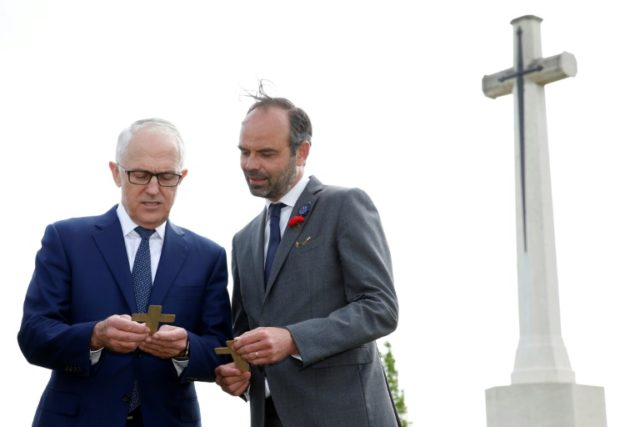 French Prime Minister Edouard Philippe (R) and Australian Prime Minister Malcolm Turnbull speak at the military cemetery in Villers-Bretonneux on the eve of ANZAC Day