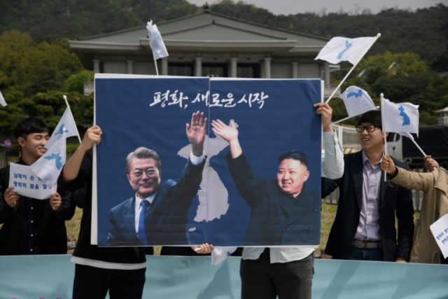 Activists hold a peace placard showing the leaders of North and South Korea at a rally in Seoul