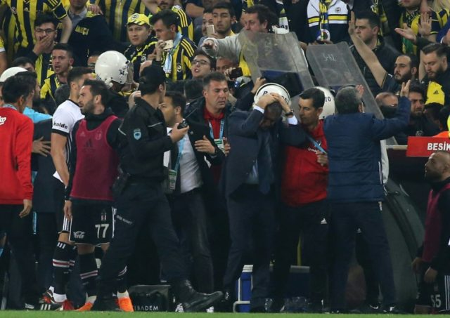 Besiktas head coach Senol Gunes (C) holds his head after being hit by an object during the Ziraat Turkish Cup semi final second leg football match between Fenerbahce and Besiktas on April 19, 2018 at Fenerbahce stadium in Istanbul