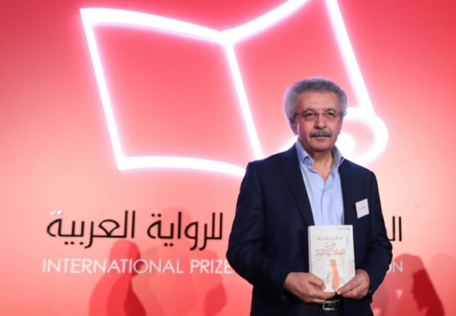 """Palestinian writer Ibrahim Nasrallah poses for a photo after winning the 2018 International Prize for Arabic Fiction for his book titled """"The Second war of the Dog"""" in Abu Dhabi on April 24, 2018"""