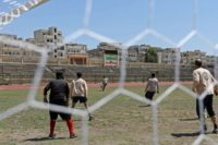 A player for the Syrian Civil Defence, known as the White Helmets, kicks the ball during the first football game at Idlib's stadium for three years, on April 25, 2018.