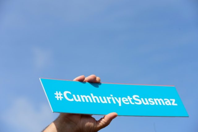 "A protestors holds a sign with the hashtag, ""Cumhuriyet will not be silent"""