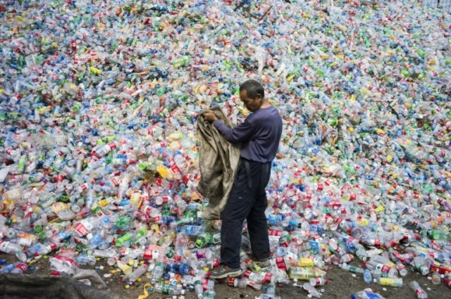 A Chinese laborer sorting plastic bottles for recycling on the outskirts of Beijing in 2015