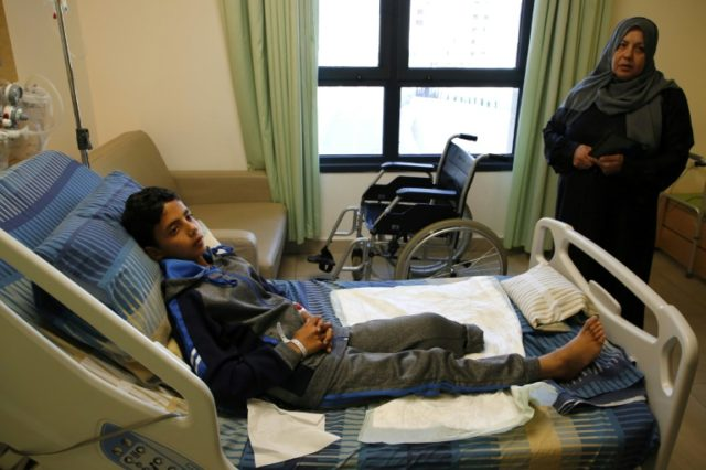 Abdel Rahman Nawfal, 12, sits in a hospital in the West Bank city of Ramallah on April 23, 2018, after his leg was amputated following an injury sustained during clashes with Israeli forces near the Gaza-Israel border