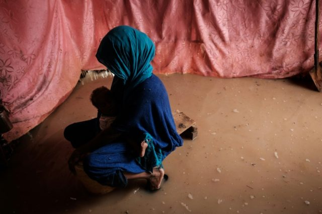 A woman holds her baby in a flooded shelter at the Dadaab complex. Nearly a quarter of million refugees and asylum seekers live in the four sprawling camps