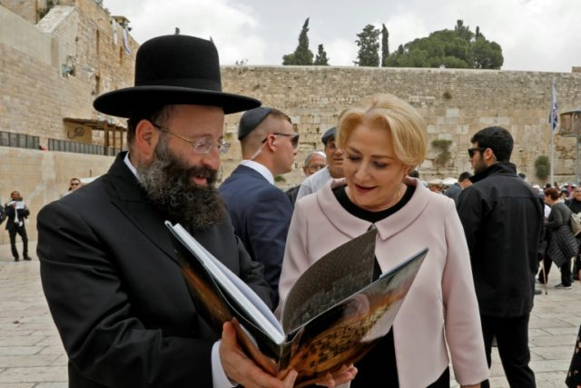 Romanian Prime Minister Viorica Dancila looks at a book on the Western Wall during a visit to the site in the Old City of Jerusalem on April 26, 2018