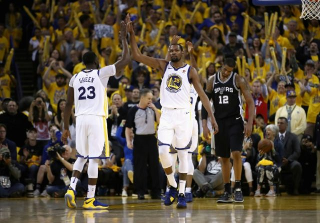 Kevin Durant (R) high fives Draymond Green as the Golden State Warriors power into the Western Conference playoff semi-finals with a 4-1 series victory over the San Antonio Spurs