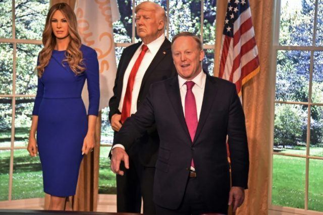 Former White House Press Secretary Sean Spicer (R) poses next to a new wax figure of the First Lady Melania Trump flanking a figure of US President Donald Trump at the Madame Tussaud's in New York City on April 25, 2018