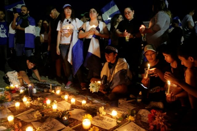 Students in Managua carry candles during a protest demanding Nicaraguan President Daniel Ortega and his wife, Vice President Rosario Murillo to step down