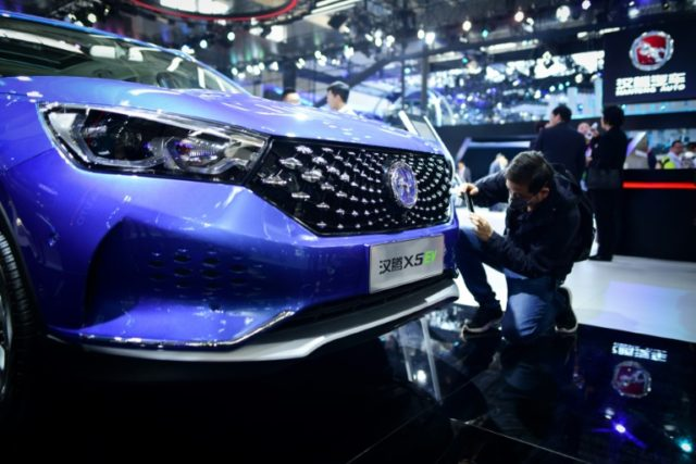 A man takes a photo of Hanteng X5 EV car at the Beijing auto show