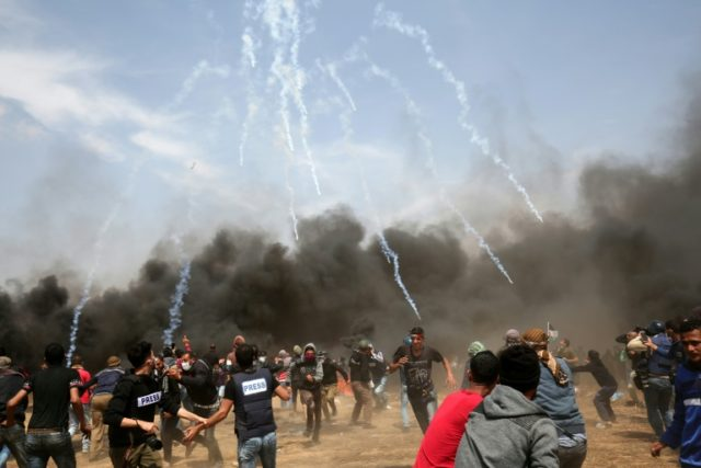 Palestinian demonstrators run for cover on April 27, 2018 during protests near the Gaza Strip's southern city of Khan Yunis
