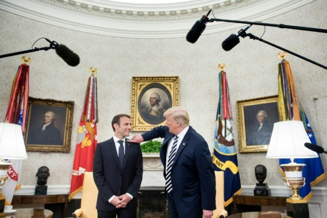 US President Donald Trump, right, brushes dandruff off French leader Emmanuel Macron's suit collar in the Oval Office