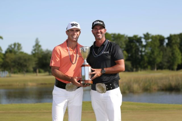 Billy Horschel (L) and Scott Piercy pose with the trophy and commerative belts after winning the Zurich Classic at TPC Louisiana on April 29, 2018