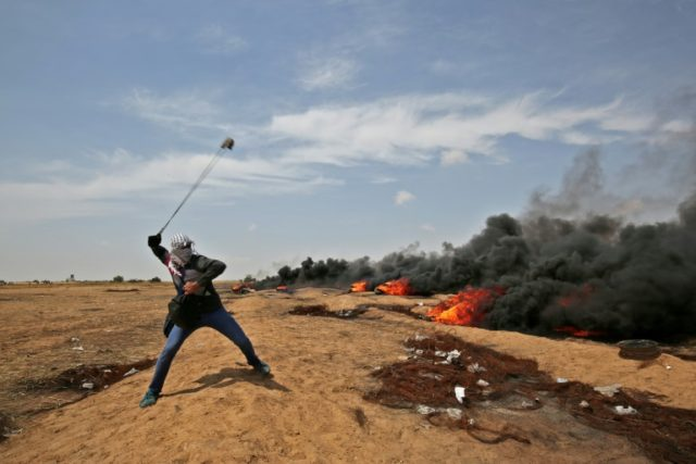A file picture shows a Palestinian demonstrator using a slingshot against Israeli security forces near Khan Yunis during protests and clashes along the Gaza-Israel border on April 27, 2018