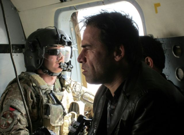 Shah Marai sits in a helicopter with a member of the International Security Assistance Force (ISAF) while on assignment in Afghanistan in 2013
