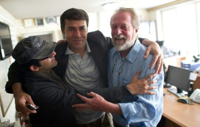 Shah Marai embraces colleagues Massoud Hossaini (L) and Lawrence Bartlett (R), after Hossaini won the Pulitzer Prize in 2012, at the AFP office in Kabul