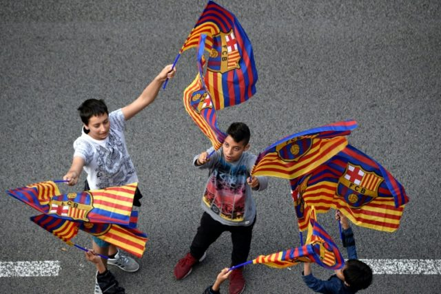 Barcelona fans wave flags at a parade on Monday to celebrate the club's 25th La Liga title.